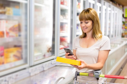 Happy female using smartphone at grocery store