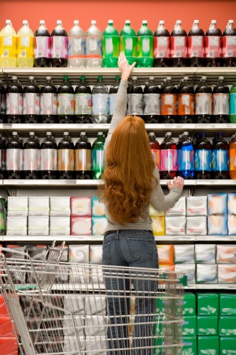 Shopper reaching for soda in aisle in supermarket